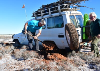 Tanami Road - 4 WD driving in the Tanami Desert, digging out a vehicle that had sunk into the match with a shovel by WA Tours driven by Otto Tours
